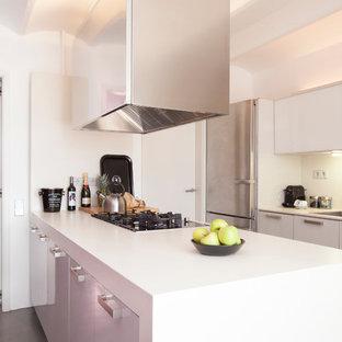 Diseño de cocina de galera, minimalista, de tamaño medio, abierta, con fregadero de un seno, armarios con paneles lisos, puertas de armario blancas, salpicadero blanco, electrodomésticos de acero inoxidable, península y encimeras blancas