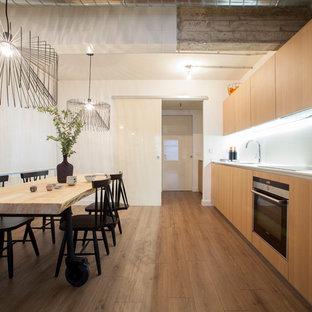 Diseño de cocina moderna con armarios con paneles lisos, puertas de armario de madera oscura, salpicadero blanco, electrodomésticos de acero inoxidable y suelo de madera en tonos medios