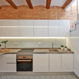 Foto de cocina mediterránea con fregadero de un seno, armarios con paneles lisos, puertas de armario blancas, salpicadero blanco, electrodomésticos de acero inoxidable, península, suelo multicolor y encimeras grises