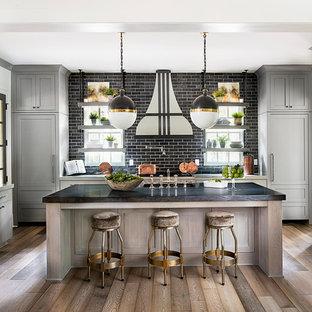 Diseño de cocina lineal, clásica renovada, de tamaño medio, abierta, con armarios estilo shaker, puertas de armario grises, salpicadero negro, salpicadero de azulejos tipo metro, electrodomésticos con paneles, suelo de madera en tonos medios, una isla y encimeras negras
