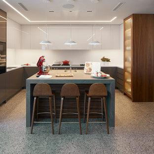 Diseño de cocina en U, actual, con fregadero bajoencimera, armarios con paneles lisos, puertas de armario grises, salpicadero blanco, una isla, suelo gris y encimeras blancas
