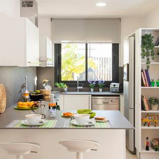 Foto de cocina en U, mediterránea, con fregadero bajoencimera, armarios con paneles lisos, puertas de armario blancas, salpicadero verde, electrodomésticos de acero inoxidable, península y encimeras grises