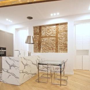 Modelo de cocina de galera, mediterránea, abierta, con armarios estilo shaker, puertas de armario grises, una isla, encimeras blancas, suelo de madera clara y suelo beige