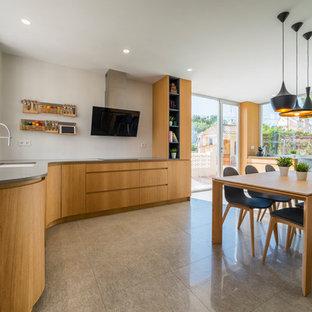 Foto de cocina comedor en L, mediterránea, con fregadero bajoencimera, armarios con paneles lisos, puertas de armario de madera clara, suelo gris y encimeras grises