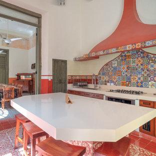 Medelhavsstil inredning av ett avskilt, mellanstort vit vitt u-kök, med en undermonterad diskho, luckor med infälld panel, skåp i mellenmörkt trä, bänkskiva i kvarts, rött stänkskydd, stänkskydd i mosaik, rostfria vitvaror, cementgolv, en köksö och rött golv