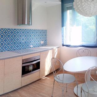 他の地域の小さい地中海スタイルのおしゃれなキッチン (ドロップインシンク、フラットパネル扉のキャビネット、淡色木目調キャビネット、クオーツストーンカウンター、青いキッチンパネル、セラミックタイルのキッチンパネル、白い調理設備、無垢フローリング、アイランドなし) の写真