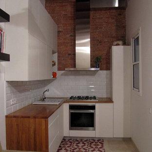 バルセロナの小さいエクレクティックスタイルのおしゃれなキッチン (白いキャビネット、木材カウンター、白いキッチンパネル、セラミックタイルのキッチンパネル、シルバーの調理設備、大理石の床) の写真