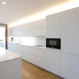 Modelo de cocina de galera, moderna, con armarios con paneles lisos, puertas de armario blancas, electrodomésticos negros, fregadero de un seno, salpicadero blanco, suelo de madera clara y encimeras blancas