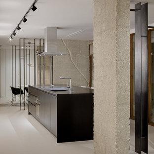 Imagen de cocina minimalista con armarios con paneles lisos, puertas de armario negras, una isla, encimeras negras, fregadero integrado, electrodomésticos negros, suelo de cemento y suelo gris