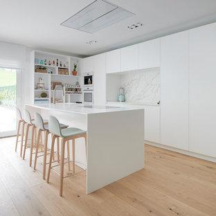 Diseño de cocina actual, grande, abierta, con fregadero integrado, armarios con paneles lisos, puertas de armario blancas, salpicadero blanco, suelo de madera clara, una isla, encimeras blancas, salpicadero de losas de piedra y electrodomésticos blancos