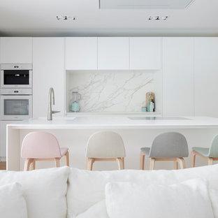 Diseño de cocina lineal, actual, grande, con fregadero integrado, armarios con paneles lisos, puertas de armario blancas, salpicadero blanco, suelo de madera clara, una isla y encimeras blancas