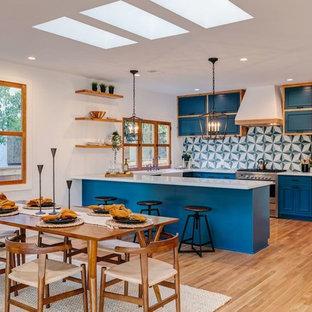 ロサンゼルスの大きいトロピカルスタイルのおしゃれなキッチン (ダブルシンク、落し込みパネル扉のキャビネット、中間色木目調キャビネット、御影石カウンター、マルチカラーのキッチンパネル、磁器タイルのキッチンパネル、シルバーの調理設備の、無垢フローリング、茶色い床、白いキッチンカウンター) の写真
