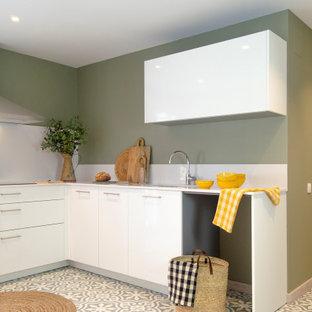 Modelo de cocina en L, contemporánea, pequeña, sin isla, con fregadero bajoencimera, armarios con paneles lisos, puertas de armario blancas, salpicadero blanco, electrodomésticos de acero inoxidable, suelo multicolor y encimeras blancas