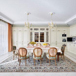 Diseño de cocina comedor en L con armarios con paneles con relieve, puertas de armario beige, salpicadero verde, electrodomésticos con paneles, suelo gris y encimeras blancas