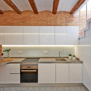 Diseño de cocina mediterránea con fregadero bajoencimera, armarios con paneles lisos, puertas de armario blancas, salpicadero blanco, salpicadero de vidrio templado, península y encimeras grises
