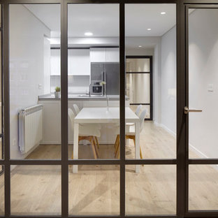 Inspiration for a mid-sized scandinavian single-wall open plan kitchen in Other with a drop-in sink, flat-panel cabinets, white cabinets, limestone benchtops, stainless steel appliances, ceramic floors and a peninsula.