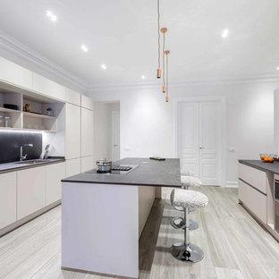 Imagen de cocina contemporánea con fregadero bajoencimera, armarios con paneles lisos, puertas de armario blancas, salpicadero negro, salpicadero de losas de piedra, electrodomésticos negros, una isla, encimeras grises y suelo beige