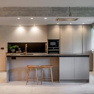 Foto de cocina de galera, moderna, con fregadero bajoencimera, armarios con paneles lisos, puertas de armario grises, electrodomésticos de acero inoxidable, una isla, suelo gris y encimeras negras