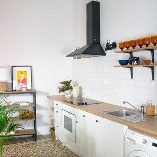 Imagen de cocina lineal, actual, pequeña, sin isla, con fregadero encastrado, armarios con paneles lisos, puertas de armario blancas, encimera de madera, salpicadero blanco, salpicadero de azulejos de porcelana, electrodomésticos blancos, suelo marrón y encimeras beige