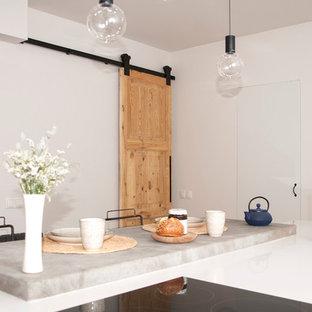 Medelhavsstil inredning av ett mellanstort kök och matrum, med vita skåp, bänkskiva i kalksten och en köksö