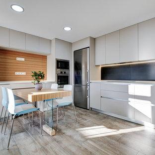 Diseño de cocina comedor en L, moderna, sin isla, con armarios con paneles lisos, salpicadero negro y electrodomésticos de acero inoxidable