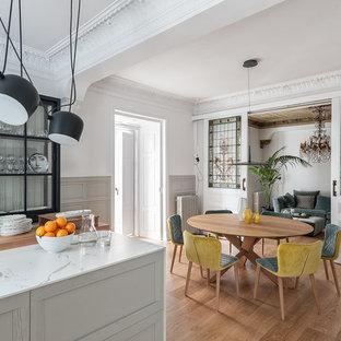Diseño de comedor de cocina bohemio, de tamaño medio, con suelo de madera clara, paredes blancas y suelo marrón
