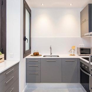 Diseño de cocina actual, pequeña, sin isla, con fregadero bajoencimera, armarios con paneles lisos, puertas de armario grises, encimera de cuarzo compacto, salpicadero blanco y electrodomésticos de acero inoxidable