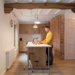Diseño de cocina rural con armarios con paneles lisos, puertas de armario de madera clara, salpicadero blanco, suelo de madera clara, una isla, suelo beige y encimeras blancas