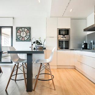 Foto de cocina comedor en U, contemporánea, de tamaño medio, con armarios con paneles lisos, puertas de armario blancas, salpicadero verde, electrodomésticos de acero inoxidable, suelo de madera clara y península