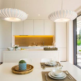 Foto de cocina comedor actual, de tamaño medio, con fregadero bajoencimera, armarios con paneles lisos, puertas de armario blancas, salpicadero marrón, electrodomésticos con paneles, una isla y encimeras blancas