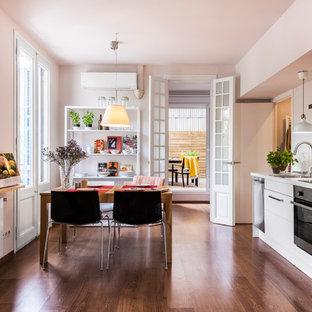 Imagen de cocina comedor lineal, actual, de tamaño medio, sin isla, con armarios con paneles lisos, puertas de armario blancas, salpicadero blanco, electrodomésticos de acero inoxidable y suelo de madera oscura