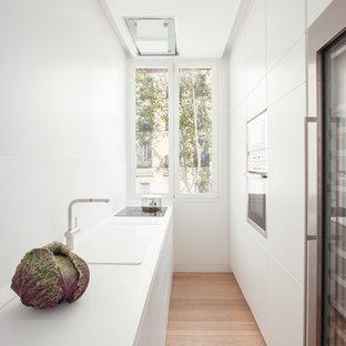 Ejemplo de cocina de galera, moderna, pequeña, cerrada, sin isla, con fregadero integrado, puertas de armario blancas, salpicadero blanco y suelo de madera clara