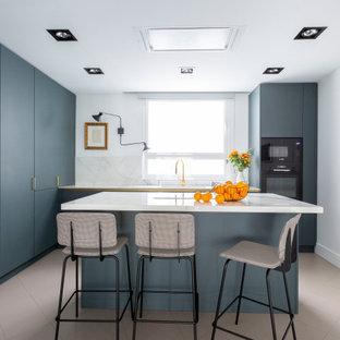 Ejemplo de cocina en L, contemporánea, de tamaño medio, cerrada, con armarios con paneles lisos, puertas de armario azules, salpicadero blanco, electrodomésticos con paneles, suelo de baldosas de porcelana, una isla, suelo gris y encimeras blancas