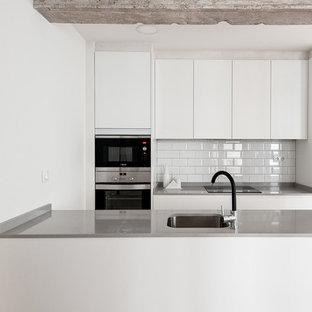 Diseño de cocina de galera, marinera, de tamaño medio, abierta, con armarios con paneles lisos, puertas de armario blancas, salpicadero blanco, salpicadero de azulejos tipo metro, electrodomésticos de acero inoxidable, península y encimeras grises