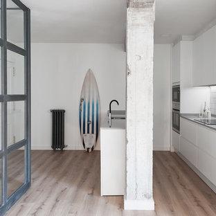 Diseño de cocina de galera, costera, de tamaño medio, abierta, con armarios con paneles lisos, puertas de armario blancas, suelo de madera en tonos medios y península
