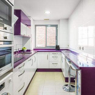 Новые идеи обустройства дома: п-образная кухня в современном стиле с врезной раковиной, плоскими фасадами, белыми фасадами, белым фартуком, техникой из нержавеющей стали, бежевым полом и фиолетовой столешницей