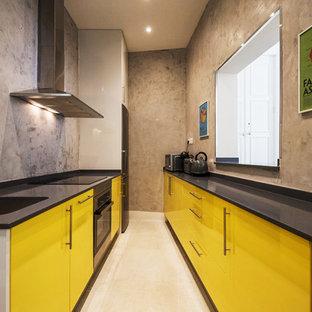Modelo de cocina de galera, contemporánea, de tamaño medio, sin isla, con fregadero bajoencimera, armarios con paneles lisos, puertas de armario amarillas, electrodomésticos de acero inoxidable, suelo beige y encimeras negras