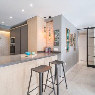 Ejemplo de cocina en L, actual, abierta, con armarios con paneles lisos, puertas de armario grises, electrodomésticos de acero inoxidable, suelo de cemento, península, suelo gris y encimeras grises