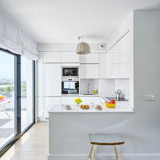 マラガの小さいビーチスタイルのおしゃれなキッチン (ドロップインシンク、フラットパネル扉のキャビネット、白いキャビネット、クオーツストーンカウンター、白いキッチンパネル、磁器タイルの床) の写真