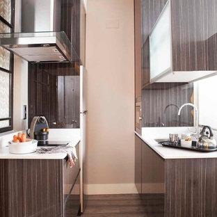 Foto de cocina de galera, contemporánea, pequeña, con armarios con paneles lisos, puertas de armario marrones, suelo de madera oscura y encimeras blancas