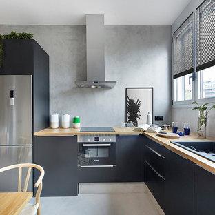Diseño de cocina comedor en L, contemporánea, sin isla, con armarios con paneles lisos, encimera de madera, electrodomésticos de acero inoxidable, fregadero de doble seno, puertas de armario negras y suelo gris