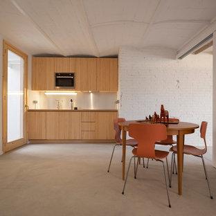 Imagen de cocina comedor lineal, contemporánea, pequeña, sin isla, con armarios con paneles lisos, puertas de armario de madera clara, electrodomésticos de acero inoxidable, suelo de cemento y suelo gris