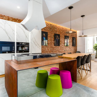 This is an example of an eclectic single-wall open plan kitchen in Madrid with black appliances, with island, flat-panel cabinets, marble floors, grey floor and orange benchtop.