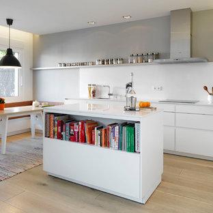 Diseño de cocina comedor lineal, actual, de tamaño medio, con armarios con paneles lisos, puertas de armario blancas, salpicadero blanco, una isla, suelo de madera clara y electrodomésticos de acero inoxidable