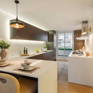 Ispirazione per una cucina ad U design chiusa e di medie dimensioni con ante lisce, ante marroni, paraspruzzi bianco, pavimento in legno massello medio, penisola, pavimento marrone, top bianco e lavello sottopiano