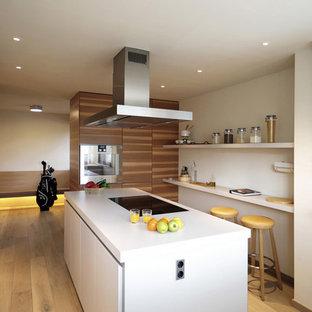Modelo de cocina lineal, contemporánea, de tamaño medio, abierta, con armarios con paneles lisos, puertas de armario de madera en tonos medios, salpicadero blanco, suelo de madera clara, península y suelo beige