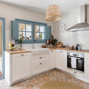 Idéer för avskilda, små medelhavsstil brunt l-kök, med en dubbel diskho, skåp i shakerstil, vita skåp, träbänkskiva, vitt stänkskydd, stänkskydd i keramik, rostfria vitvaror, cementgolv och flerfärgat golv