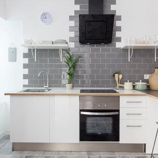 Imagen de cocina en L, escandinava, de tamaño medio, abierta, con armarios con paneles lisos, puertas de armario blancas, encimera de madera, salpicadero verde, salpicadero de azulejos tipo metro, electrodomésticos de acero inoxidable, fregadero encastrado y península