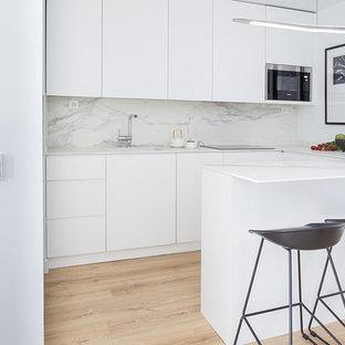 Modelo de cocina en U, contemporánea, con fregadero bajoencimera, armarios con paneles lisos, puertas de armario blancas, suelo de madera clara, península, encimeras blancas y suelo beige