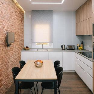 マドリードのコンテンポラリースタイルのおしゃれなL型キッチン (アンダーカウンターシンク、フラットパネル扉のキャビネット、グレーのキャビネット、白いキッチンパネル、サブウェイタイルのキッチンパネル、シルバーの調理設備、濃色無垢フローリング、茶色い床) の写真